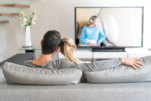 Loving couple watching tv at home stock photo