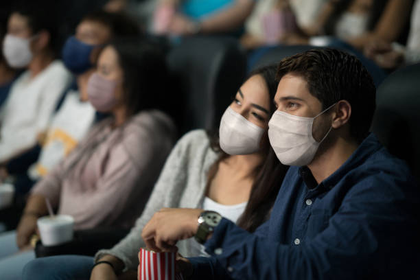 Loving couple wearing facemasks on a date at the cinema stock photo