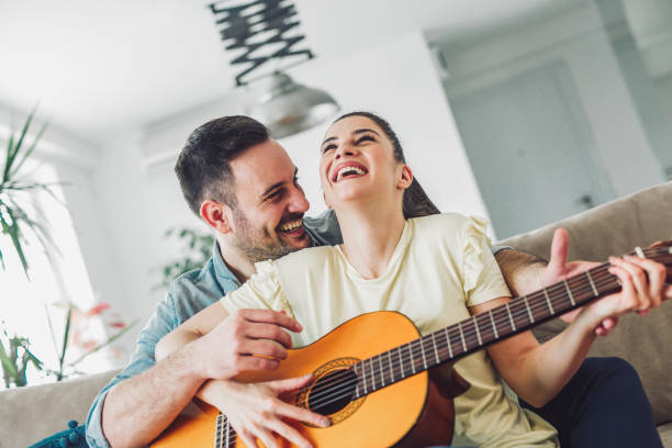 Loving couple with guitar in the room at home Loving couple with guitar in the room at home serenading stock pictures, royalty-free photos & images