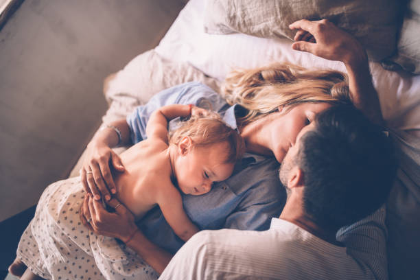 Loving couple with sleeping baby kissing in bed stock photo