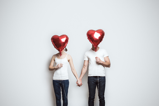 A young couple wearing white shirts and blue jeans hold red heart shaped balloons to celebrate the Valentine holiday.  They hold hands, their faces obscured by the balloons.  Horizontal image white background and copy space.