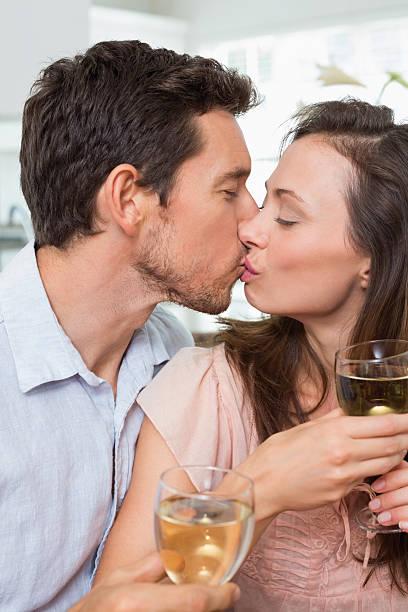 coppia di innamorati baciarsi con bicchieri di vino a casa - brunette woman eyeglasses kiss man foto e immagini stock