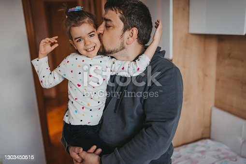 Loving dad kissing his cute smiling little daughter, enjoying time together at home