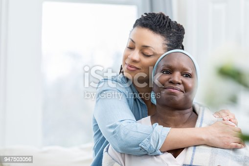 932074776 istock photo Loving daughter embraces aging mother 947503056