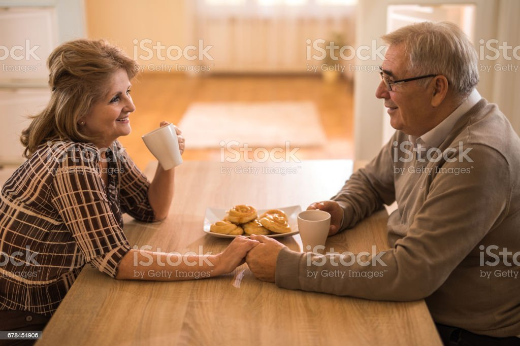 Loving elderly couple holding hands and communicating during coffee time. royalty-free stock photo