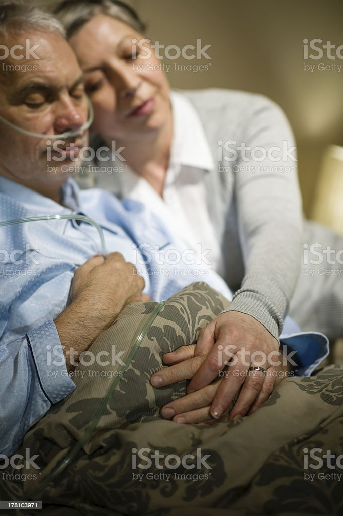 Loving elderly couple sleeping in bed stock photo