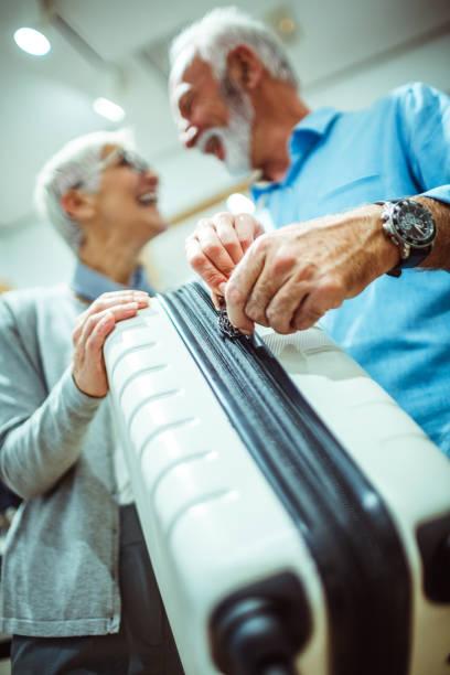 ältere liebespaar entpacken zusammen einen weißen reise koffer im ladengeschäft taschen und accessoires - trolley kaufen stock-fotos und bilder