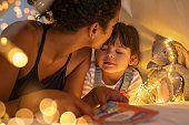 istock Loving ethnic mother kissing daughter in cozy hut 1270067152