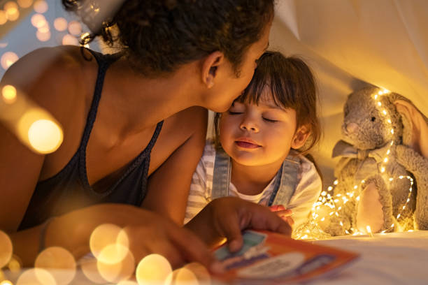 Loving ethnic mother kissing daughter in cozy hut stock photo