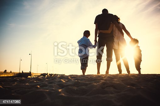 A silhouette of a beautiful young family on vacation at Venice beach, California watching the sun set over the ocean, the Venice Fishing Pier visible behind them.  The parents hug, holding the hands of their children.  Horizontal with copy space.