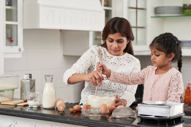 Loving Family Cooking Delicious Pie Attractive middle-aged woman and her cute little daughter beating eggs and flour with whisk while making delicious pie at home, interior of small kitchen on background indian family stock pictures, royalty-free photos & images