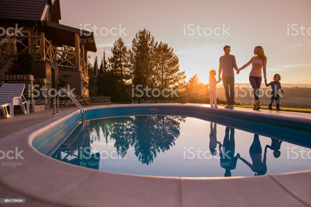 Loving family holding hands and walking by the pool at sunset. stock photo