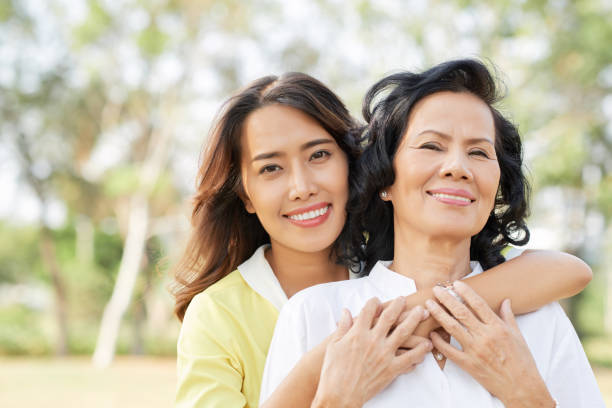 Loving family Portrait of happy senior Vietnamese woman and her adult daughter hugging in summer park vietnamese ethnicity stock pictures, royalty-free photos & images
