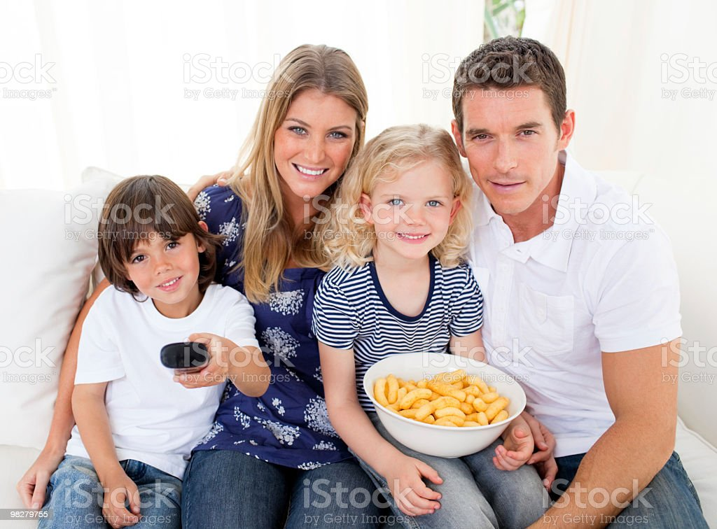Loving family watching television sitting on sofa royalty-free stock photo