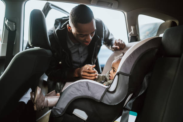 Loving Father Buckles Daughter in Car Seat stock photo