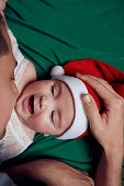 Little baby girl lying on her back on green bed, wearing Christmas hat and screaming; father touching her head