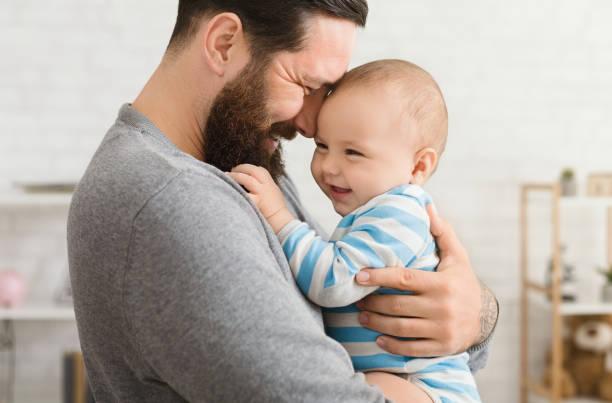 liebevolle vater umarmt seinen niedlichen baby-sohn - genderblend stock-fotos und bilder