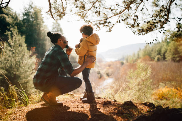 Loving father having fun with son in forest stock photo