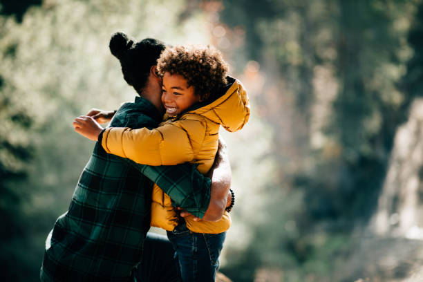 Loving father hugging son in nature park stock photo
