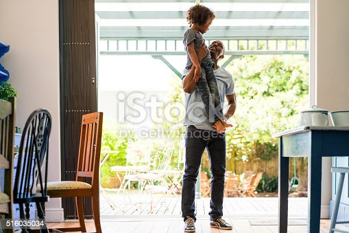 istock Loving father lifting girl at home 516035034