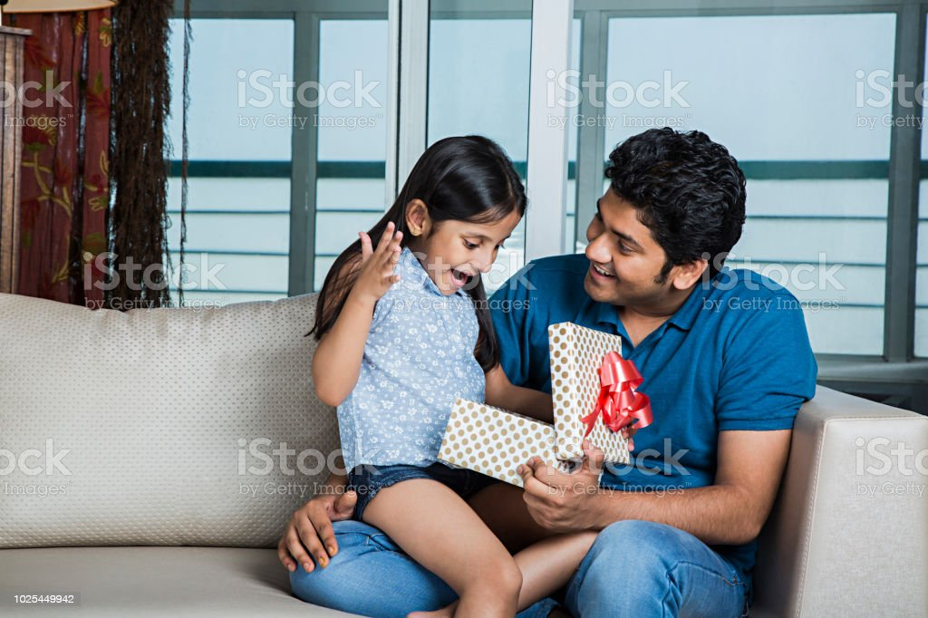 Loving Father Presenting Gift To Smiling Daughter