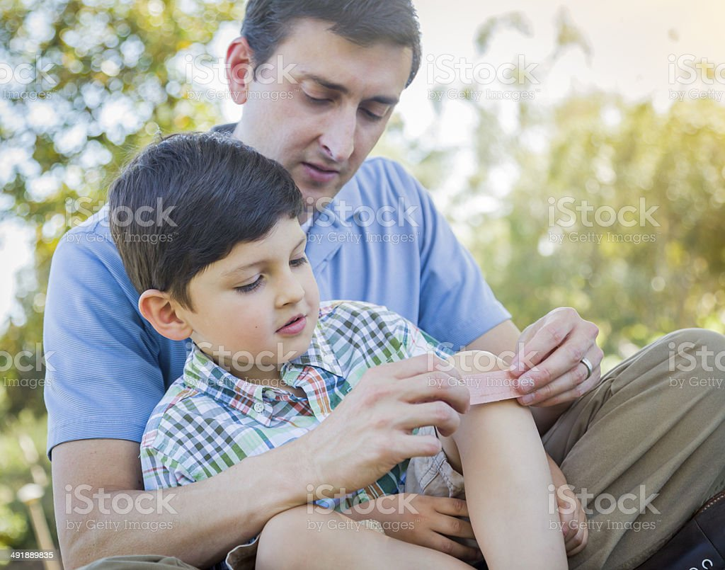 Loving Father Puts Bandage on Knee of Young Son stock photo