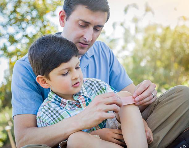 Amour père est Bandage sur le genou de Son jeune fils - Photo