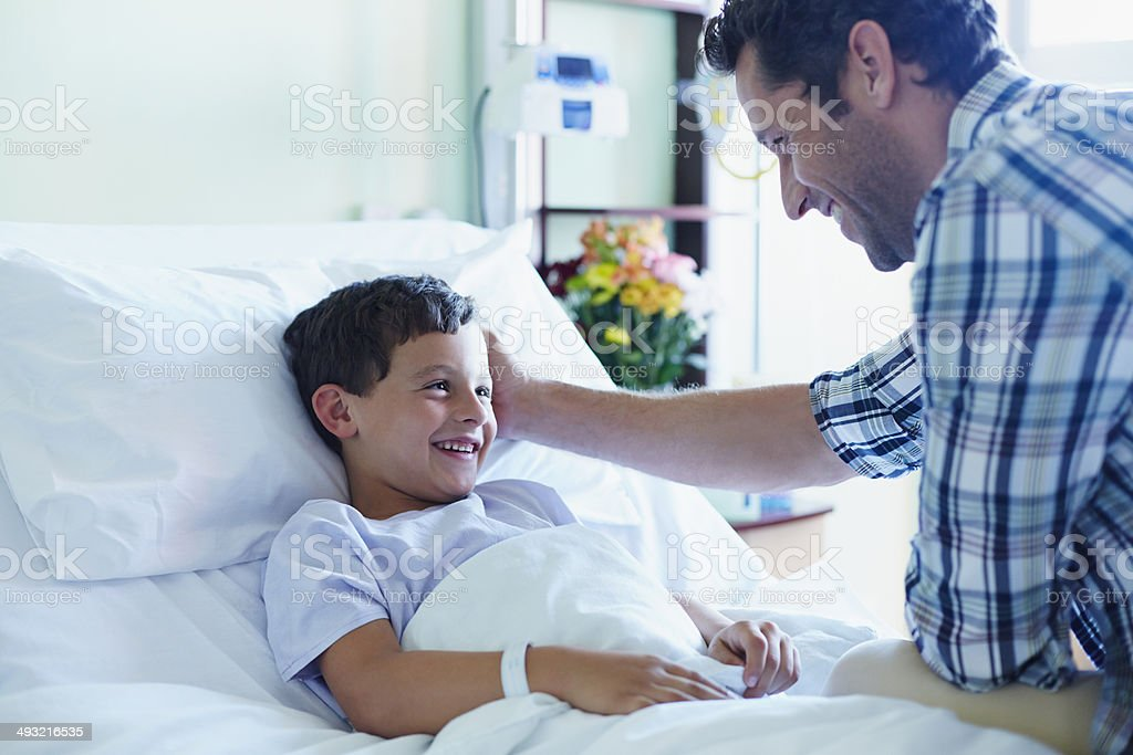 Loving father looking at ill son in bed at hospital ward