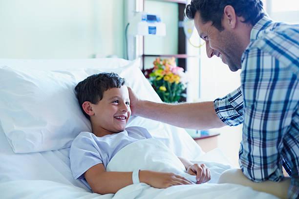 loving father with ill son in hospital ward - bett für jungs stock-fotos und bilder