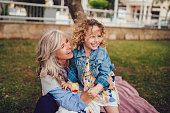 Happy grandmother and little granddaughter embracing, having fun and playing together in park