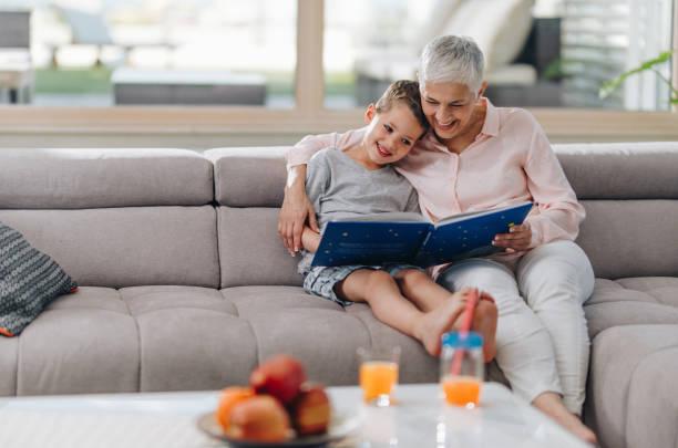 liebevolle oma ihrem enkel zu hause ein buch zu lesen. - seniorenwohnungen stock-fotos und bilder