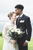 A smiling groom stands outdoors with his bride on their wedding day.  They put an arm around each other as he closes his eyes and presses his face to her forehead.  There is a scenic background.