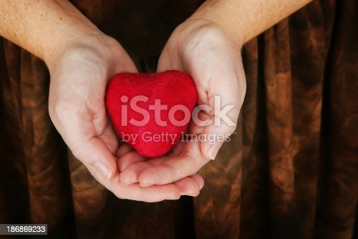 A woman's hands holding a small felted heart (made by me).