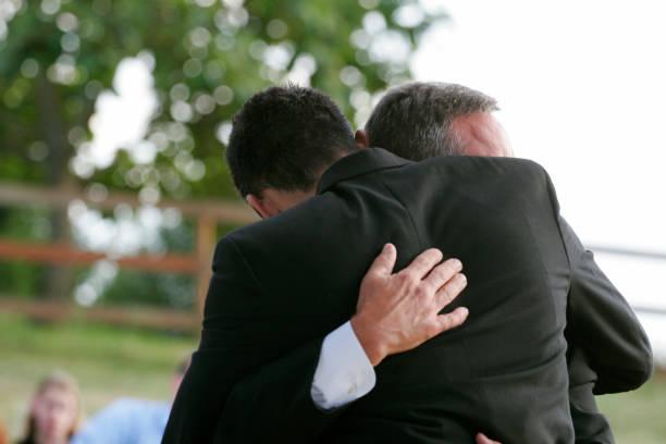 liebevolle umarmung von freunden/vater und sohn - hochzeitsanzug herren stock-fotos und bilder