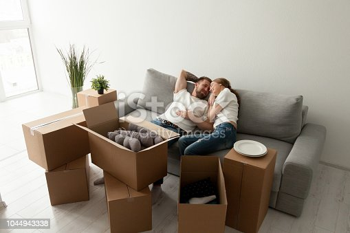 938682826istockphoto Loving husband lying together on sofa in first shared flat 1044943338