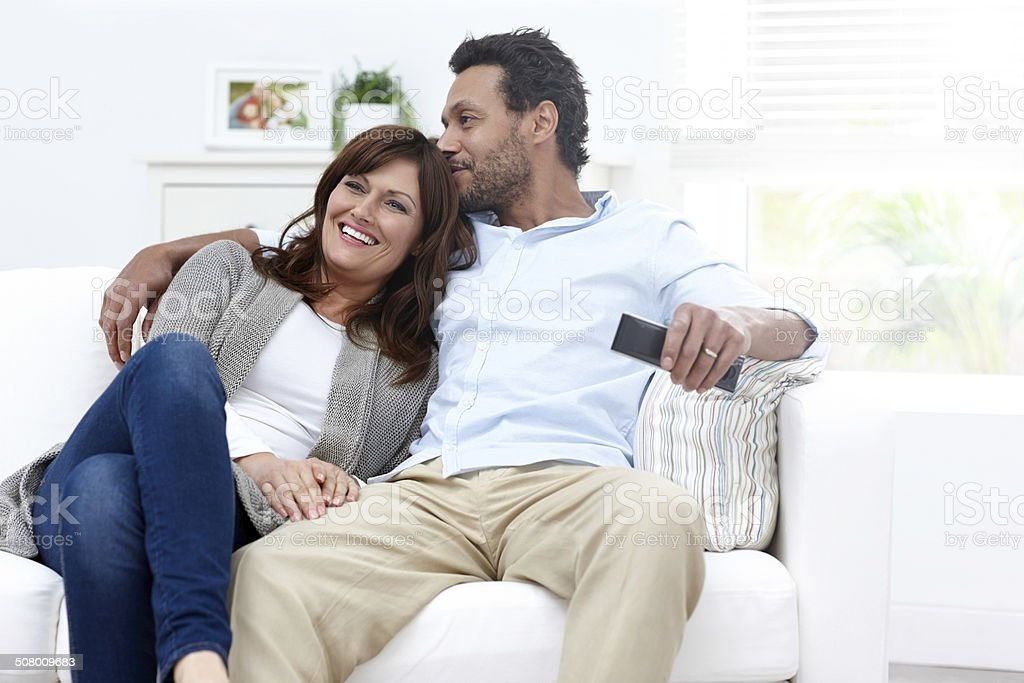 Loving interracial couple sitting on sofa watching TV stock photo