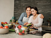A loving latin mother teaching her teenage daughter how to cook.