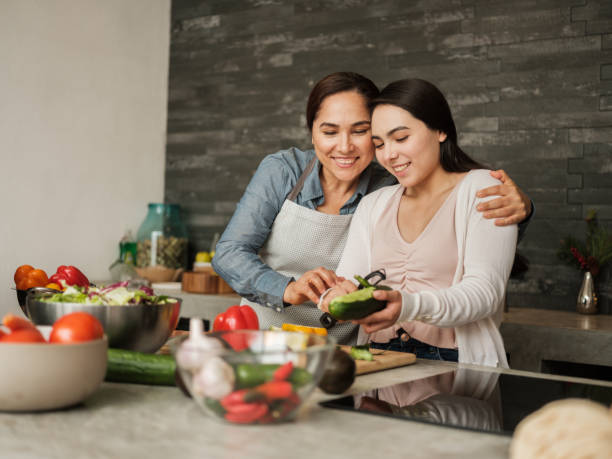 Loving latin mother teaching daughter to cook at home stock photo