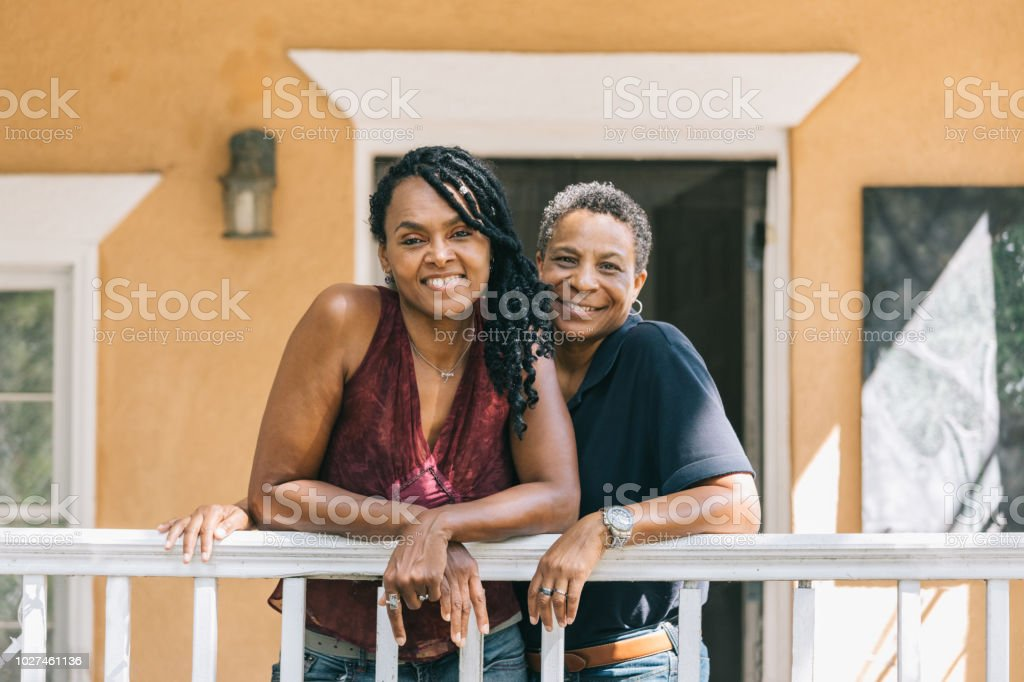 loving lesbian couple posing on the porch stock photo