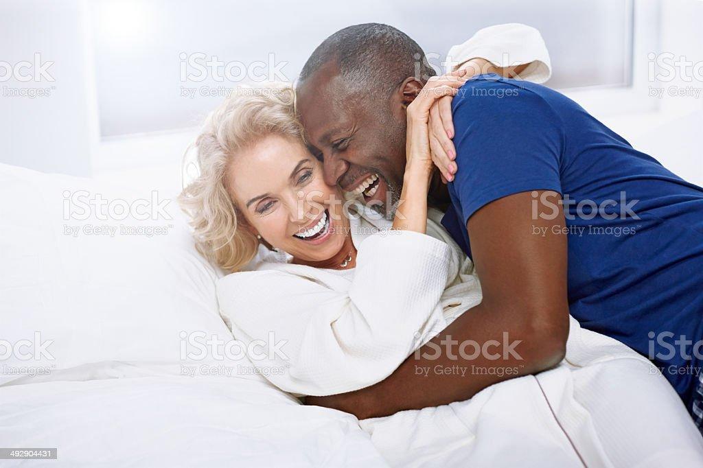 Loving mature couple having fun on bed stock photo