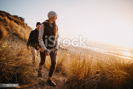 A senior couple explores a beach in Oregon state, enjoying the beauty of sunset on the Pacific Northwest coast.  They hike up a sand dune, the ocean visible in the background.