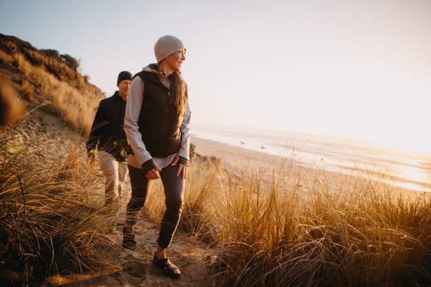 Loving Mature Couple Hiking At Oregon Coast A senior couple explores a beach in Oregon state, enjoying the beauty of sunset on the Pacific Northwest coast.  They hike up a sand dune, the ocean visible in the background. lifestyles stock pictures, royalty-free photos & images