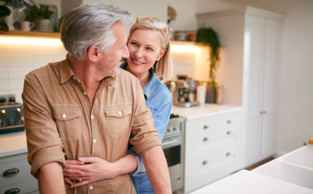 Loving Mature Couple Hugging As They Stand By Counter In Kitchen At Home stock photo