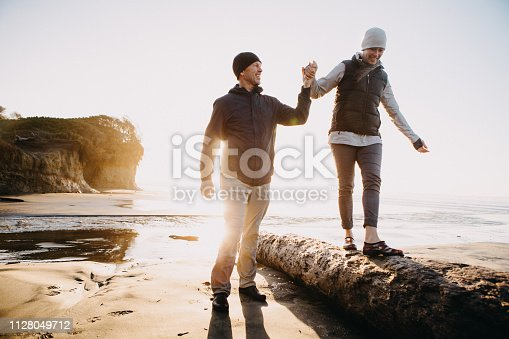 A senior couple explores a beach in Oregon state, enjoying the beauty of sunset on the Pacific Northwest coast.  The man holds the womans hand as she balances on a log, the sun glowing over the ocean behind them.