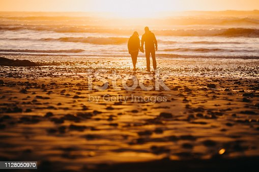 A senior couple explores a beach in Oregon state, enjoying the beauty of sunset on the Pacific Northwest coast.  They walk hand in hand, the ocean visible behind them.