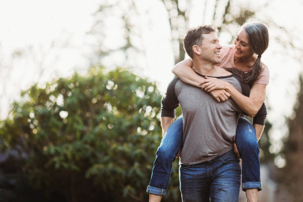 Loving Mature Couple Playing Outdoors A cute couple in their mid 50's enjoy some fresh air and exercise outside together, walking through the streets of their neighborhood.  The husband carries his wife on his back. piggyback stock pictures, royalty-free photos & images