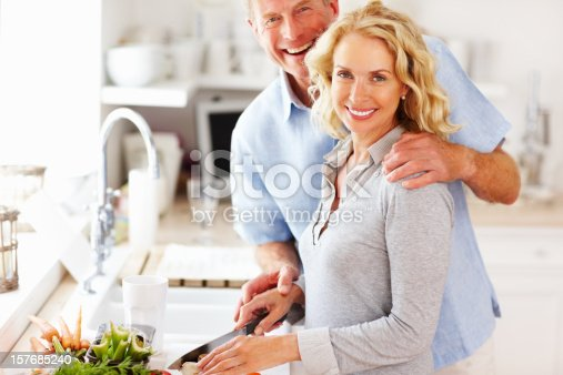 istock Loving mature couple preparing food together in the kitchen 157685240