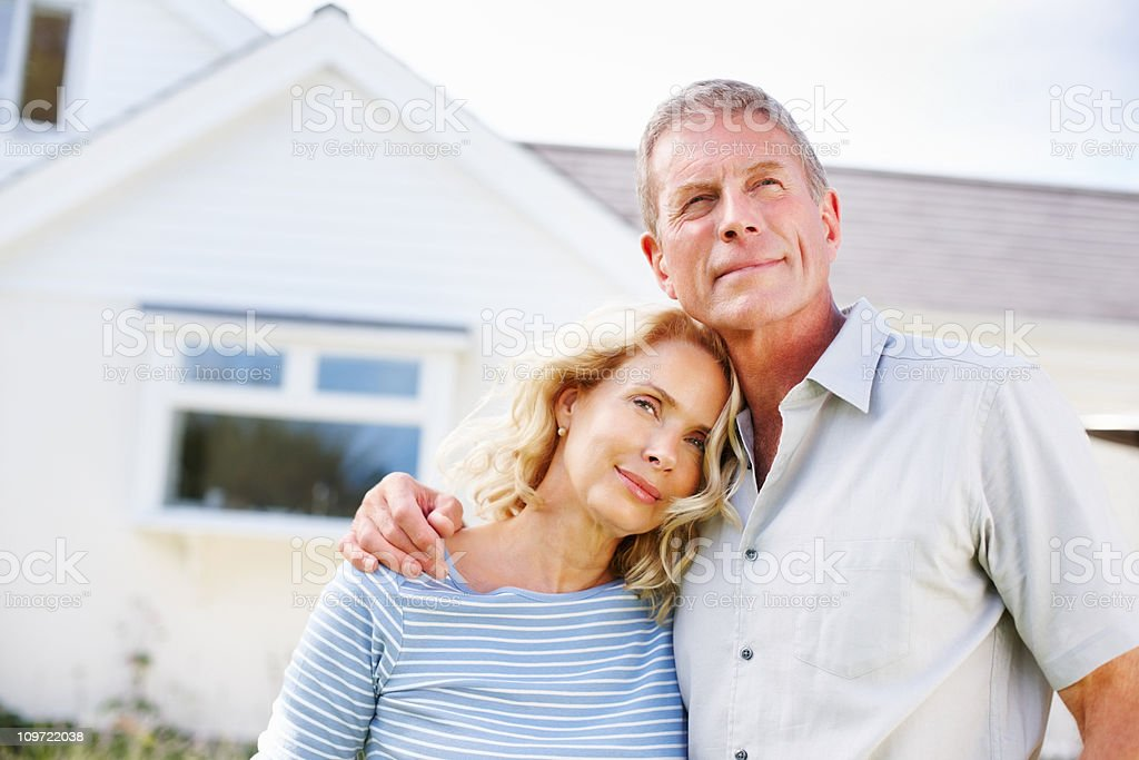 Loving mature couple standing in front of their house royalty-free stock photo