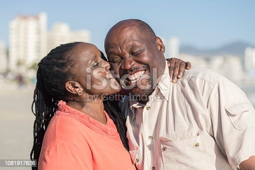 Portrait of man with toothy smile laughing, wife giving him a kiss, arm around, happiness, togetherness, love