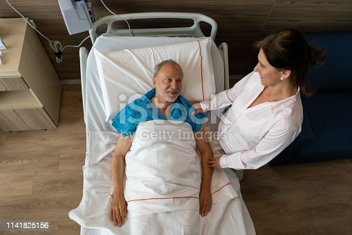 Loving mature woman visiting partner at the hospital lying doen on bed while talking and smiling - High angle view